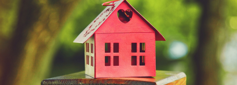 Rood model van het huis als symbool op de natuurlijke tuin achtergrond, prinsjesdag, Miljoenennota, wonen, huis, hypotheek
