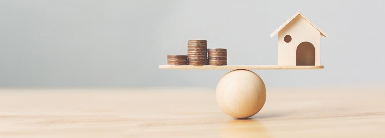 Houten huis en geld munten op hout schaal. Investeringen huis hypotheek