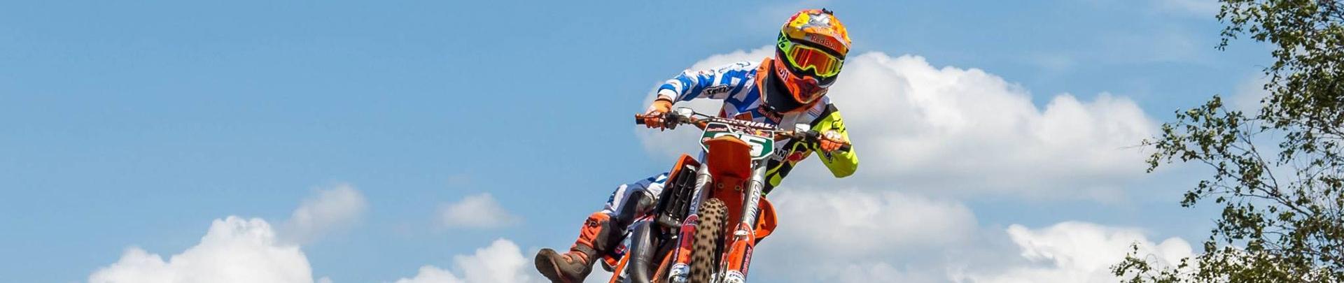 Jonge motorcoureur met zijn motor zwevend in de lucht